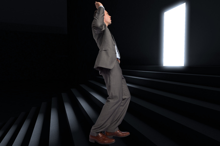 Businessman posing with hands up against steps leading to light in the darkness photo