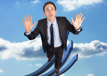flechas curvas: Hombre de negocios posando con los brazos levantados contra flechas curvas azules apuntando hacia arriba contra el cielo Foto de archivo