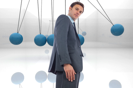 Stern businessman standing against blue newtons cradle photo