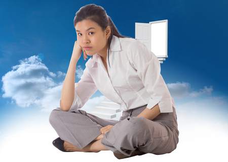 slumped: Businesswoman sitting cross legged against steps leading to open door in the sky Stock Photo