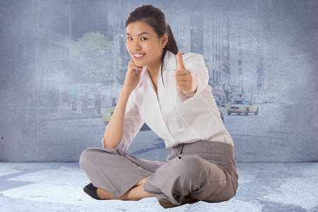 Businesswoman sitting cross legged showing thumb up against urban projection on wall