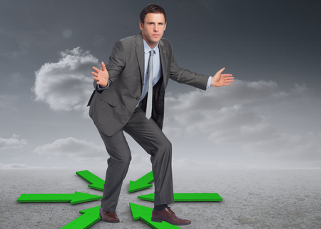 Businessman standing with arms out against green arrows in a desert landscape photo