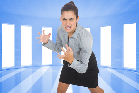Furious businesswoman gesturing against bright blue room with windows Stock Photo