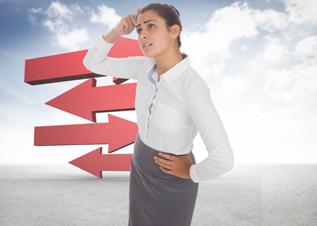 Worried businesswoman against red arrows in a desert landscape Stock Photo - 26778952