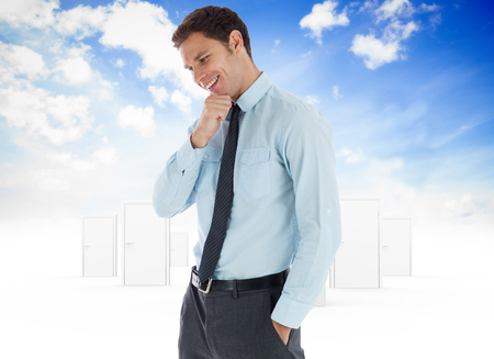 Thoughtful businessman with hand on chin against opening door in sky photo