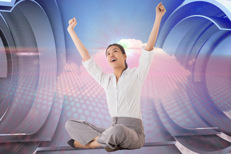 Businesswoman sitting cross legged cheering against cloud design on a futuristic structure photo