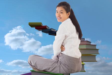 Businesswoman sitting cross legged smiling against book steps against sky photo