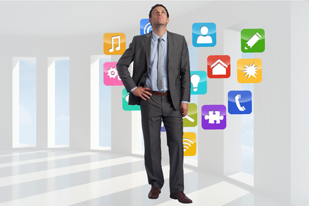 light brown hair: Serious businessman with hand on hip against application icons in room