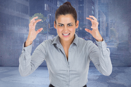 Furious businesswoman gesturing against urban projection on wall photo
