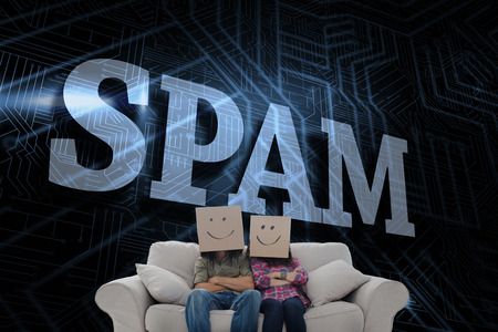 unsolicited: The word spam and silly employees with arms folded wearing boxes on their heads against futuristic black and blue background Stock Photo