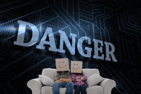 The word danger and silly employees with arms folded wearing boxes on their heads against futuristic black and blue background photo