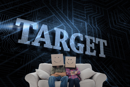The word target and silly employees with arms folded wearing boxes on their heads against futuristic black and blue background photo