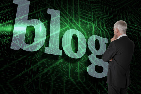The word blog and thoughtful businessman standing back to camera against green and black circuit board photo