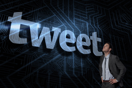 The word tweet and serious businessman with hands on hips against futuristic black and blue background Stock Photo - 26800467