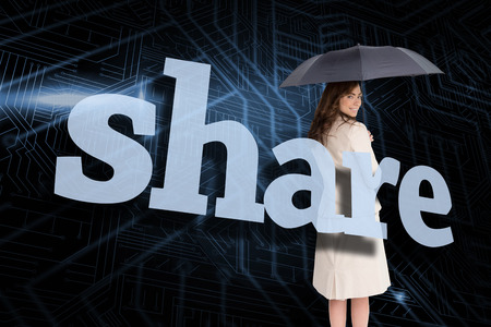 Businesswoman holding umbrella behind the word share against circuit board photo