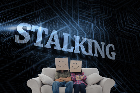stalking: The word stalking and silly employees with arms folded wearing boxes on their heads against futuristic black and blue background Stock Photo