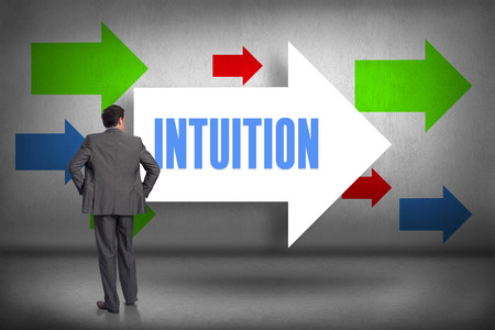 intuition: The word intuition and businessman with hands on hips against arrows pointing