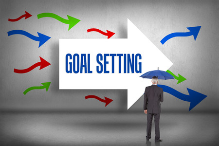 The word goal setting and businessman holding umbrella against arrows pointing photo