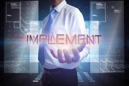 implement: Uomo d'affari che presenta la parola attuare contro ologramma su sfondo nero con piazze