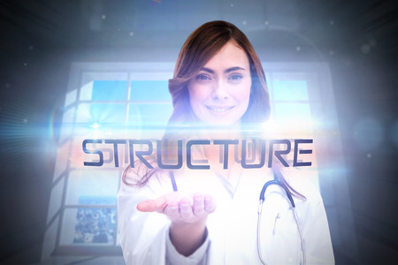 The word structure and portrait of female nurse holding out open palm against room with large window showing city photo