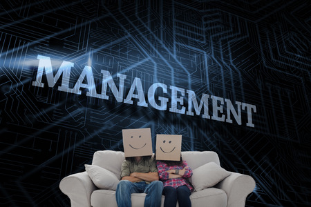 The word management and silly employees with arms folded wearing boxes on their heads against futuristic black and blue background photo