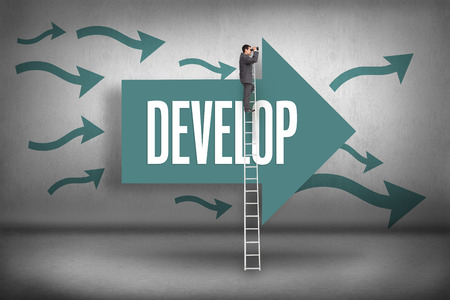 The word develop and businessman standing on ladder using binoculars against arrows pointing photo