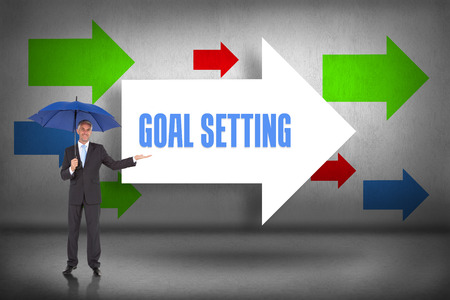 The word goal setting and peaceful businessman holding blue umbrella against arrows pointing Stock Photo