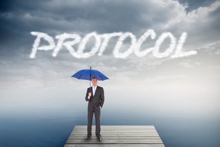 The word protocol and businessman smiling at camera and holding blue umbrella against cloudy sky over ocean photo