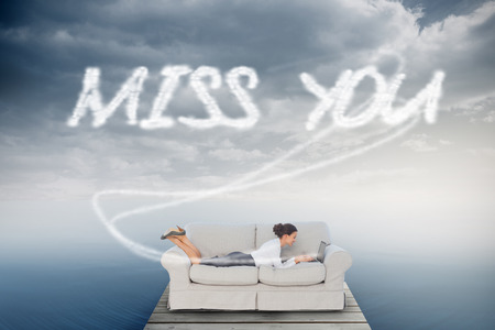 The word miss you and business woman lying on couch against cloudy sky over ocean photo