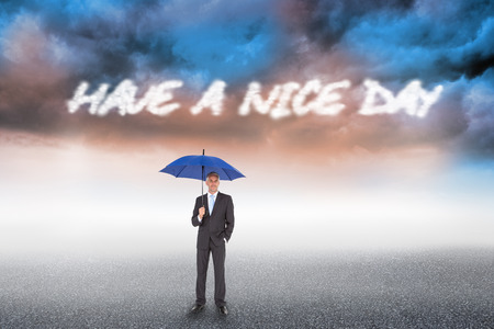 The word have a nice day and businessman smiling at camera and holding blue umbrella against cloudy landscape background photo