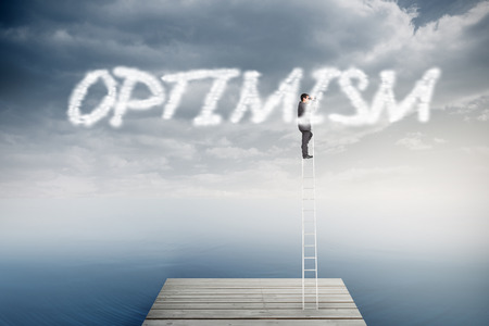 The word optimism and businessman standing on ladder using binoculars against cloudy sky over ocean photo