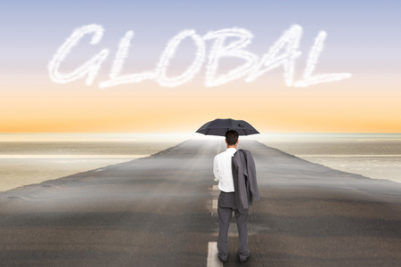 The word global and businessman standing back to camera holding umbrella and jacket on shoulder against road leading out to the horizon photo
