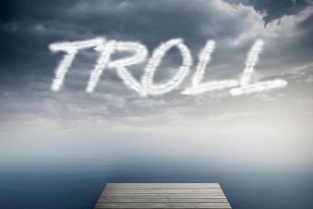 The word troll against cloudy sky over ocean