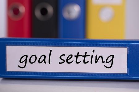setting goal: The word goal setting on blue business binder