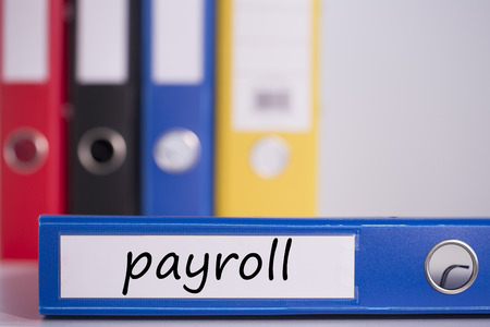 payroll: The word payroll on blue business binder Stock Photo