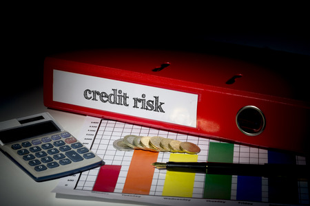 credit risk: The word credit risk on red business binder on a desk Stock Photo