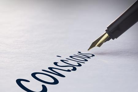 conscious: Fountain pen writing the word conscious Stock Photo