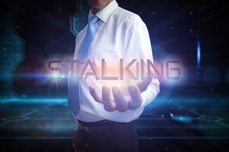 Businessman presenting the word stalking against doorway on technological black background photo