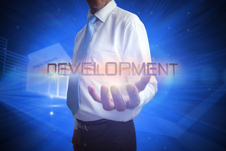 Businessman presenting the word development against shiny statistic on blue background photo