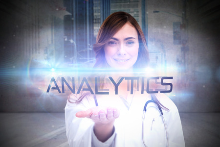 The word analytics and portrait of female nurse holding out open palm against urban projection on wall