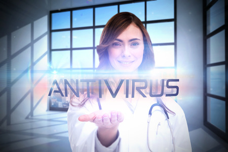 The word antivirus and portrait of female nurse holding out open palm against room with large window showing city photo