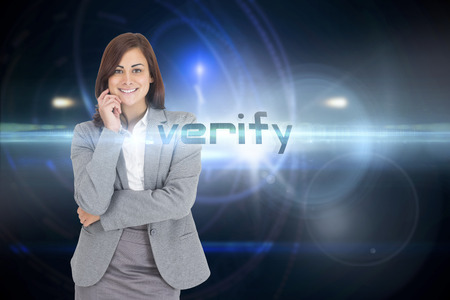The word verify and smiling thoughtful businesswoman against futuristic black background with circles Stock Photo