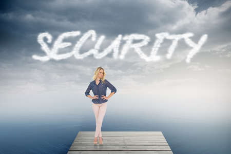The word security and thoughtful gorgeous blonde wearing classy clothes posing against cloudy sky over ocean photo