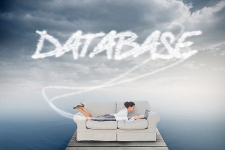 The word database and business woman lying on couch against cloudy sky over ocean photo