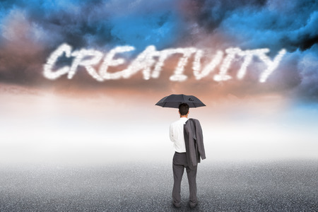 The word creativity and businessman standing back to camera holding umbrella and jacket on shoulder against cloudy landscape background photo