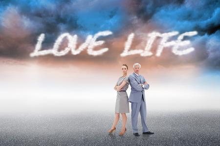 love of life: La vita e la parola amore serio imprenditore in piedi back to back con una donna contro nuvoloso sfondo del paesaggio