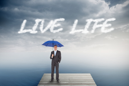 The word live life and businessman smiling at camera and holding blue umbrella against cloudy sky over ocean photo