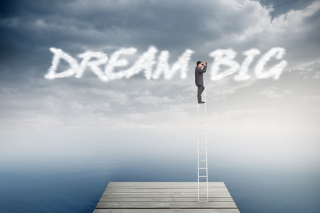 The word dream big and businessman standing on ladder using binoculars against cloudy sky over ocean photo