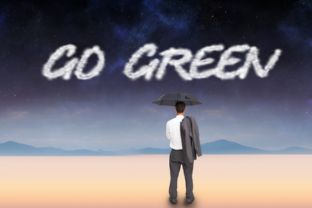The word go green and businessman standing back to camera holding umbrella and jacket on shoulder against serene landscape photo