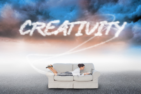 The word creativity  and business woman lying on couch against cloudy landscape background photo